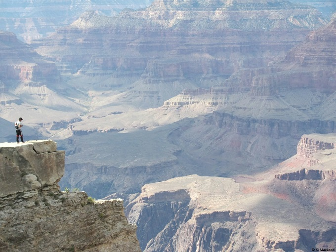 A single person standing at the edge of the Grand Canyon