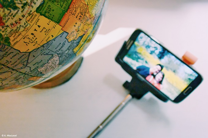 Globe and selfie sticks on white surface