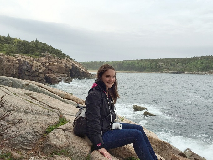 Sitting at the edge of the cliffs in Acadia National Park
