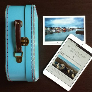 Suitcase, ipad, and postcard on a table