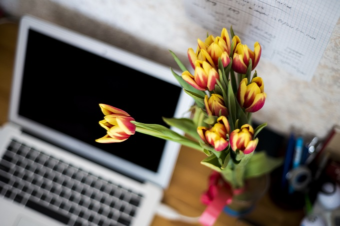 Flowers and a laptop on a desk