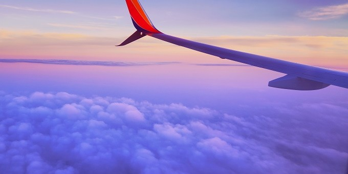 plane-wing-above-the-clouds-at-sunset